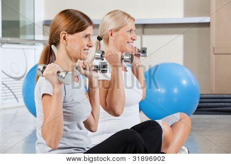 Two happy senior women using dumbbells for exercise in gym