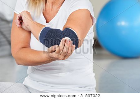 Woman with joint pain and bandage in gym