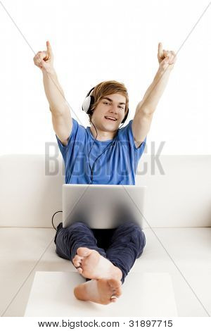 Happy young man sitting on the couch with arms up and a laptop over the legs