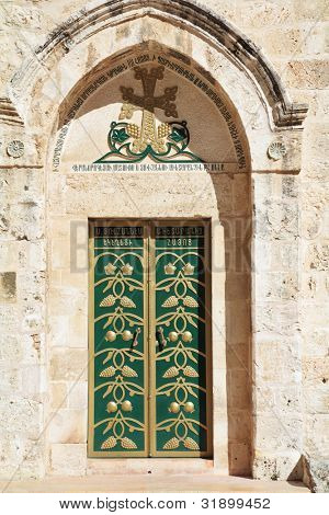 Entrance to the Coptic Church of the Holy Sepulchre in Ierusalime.Green doors are decorated by gold grape clusters and pomegranates