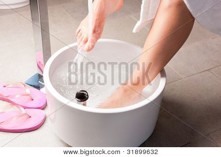 Woman having hydrotherapy water footbath in spa setting