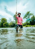 Man Fishing And Relaxing While Enjoying Hobby. Happy Fisherman Fishing In River Holding Fishing Rods poster