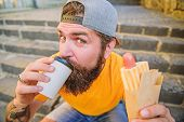 Junk Food. Carefree Hipster Eat Junk Food While Sit Stairs. Snack For Good Mood. Guy Eating Hot Dog. poster