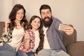 Use Smartphone For Selfie. Friendly Family Having Fun Together. Mom Dad And Daughter Relaxing On Cou poster