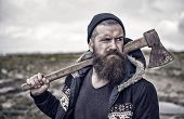 Bearded Man Hold Rusty Axe On Natural Background. Hipster In Hat And Jacket Outdoor. Man With Beard  poster