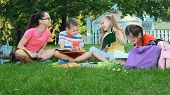 Children And Education, A Group Of Schoolchildren Doing Homework On The Lawn. poster