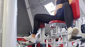 A Woman In Sportive Clothes Training In The Gym - Training Her Legs On The Butterfly Training Appara poster