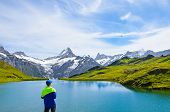 Young Man Operating The Flying Drone Over Beautiful Bachalpsee In The Swiss Alps. Drone Cameras Are  poster