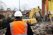 Engineer Mans In Helmet And Jacket Controlling Outdoor Construction Site. Engineerin Demolition Site poster