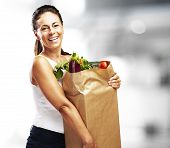 picture of grocery-shopping  - middle aged woman smiling and holding the purchase indoor - JPG
