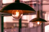 Incandescent Lamps In A Modern Cafe. Edison Lamp. Close Up Two Yellow Lamp In Cafe At Night poster