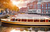 Amsterdam, Holland, Netherlands. Amstel river, canals and boats against evening dusk sunset sky city poster