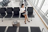 Young Woman Working On Laptop Sitting In A Departure Lounge Of Airport poster