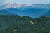 Top View Of The Mountain Range And Peaks Covered With Snow. Mountain Peak In The Summer. Low Buildin poster