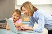 Mother and daughter using laptop in domestic kitchen poster