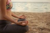 Lotus Yoga Pose. Close Up. Focus On One Hand. Yoga At The Beach. Young Woman Sitting On Sand, Medita poster