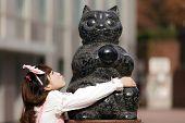 stock photo of lolita  - japanese lolita hugging cat statue in Tokyo - JPG