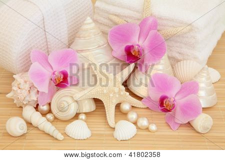 Spa accessories with pink orchid flower group, sea shells, pearls, white towels and linen covered sponge over bamboo background.