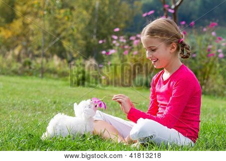Puppy, kid - lovely girl playing with cute puppy in the garden