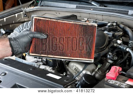 An auto mechanic wearing protective work gloves holds a dirty, clogged air filter over a car engine during general auto maintenance.