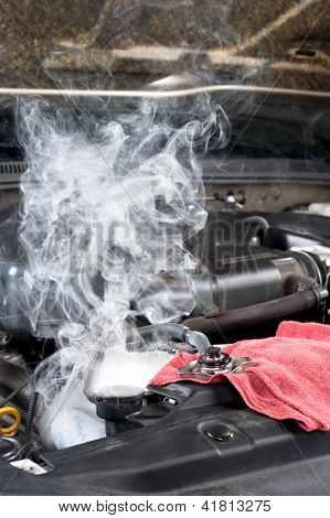 An overheated car engine smokies as the radiator cools down.