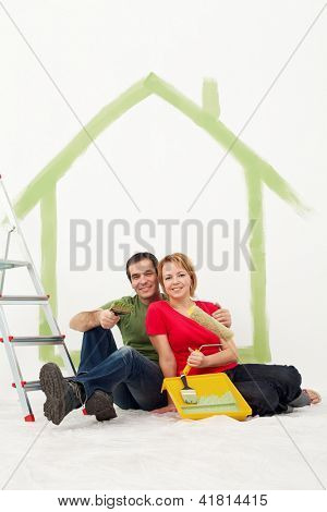 Couple with painting utensils resting in their home - redecorating concept