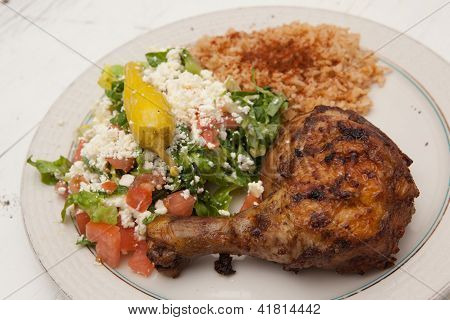 Mediterranean style chicken dinner with salad and rice