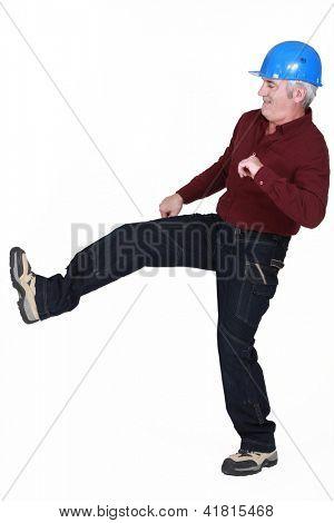 Construction worker kicking something