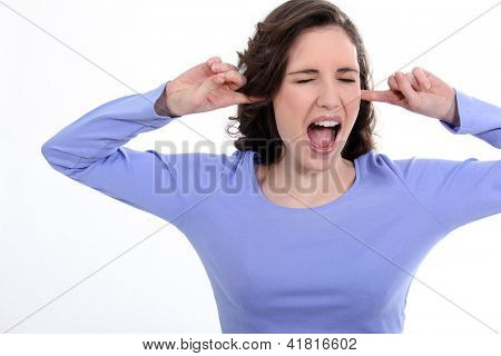 Woman stood with fingers in ears