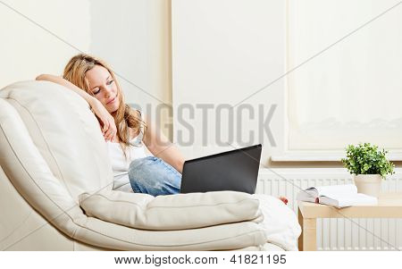 Pretty Young Woman Sitting On Sifa With Laptop