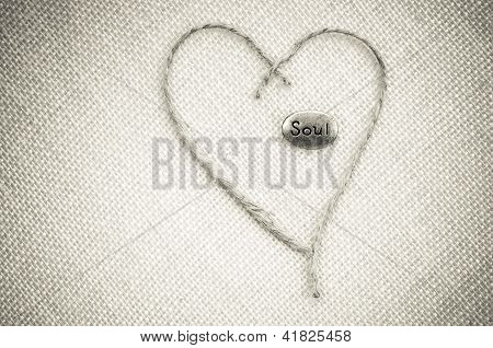 silver oval soul stone on tan burlap with hemp rope twine heart