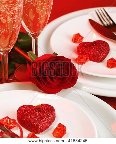 Image of luxury table setting, festive white utensil served with knife and fork, two glasses for champagne, holiday dinner decorated with red rose and romantic candle, Valentine day, love concept