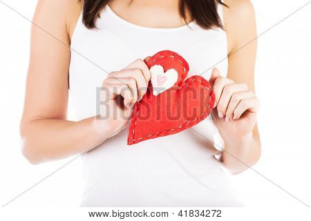 Picture of big red heart in hands, female holds handmade sewn soft toy, macro, shallow dof, woman with Valentine gift, conceptual image of health care and love