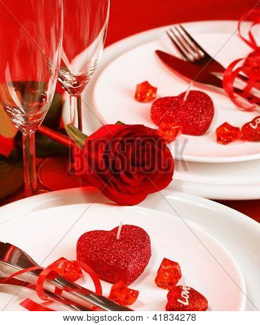 Picture of beautiful romantic table setting, luxury white plates served with silverware and glasses for wine and decorated with red rose flower and heart-shaped candles, Valentine day, love concept