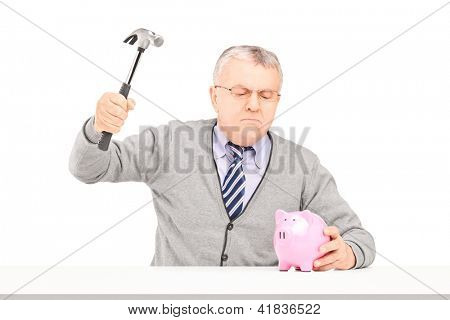 Angry mature man trying to break a piggy bank with a hammer isolated on white background