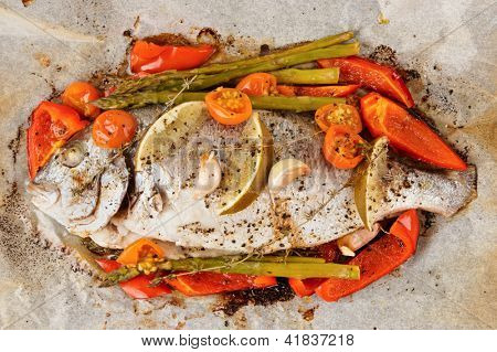 Dorade with vegetables roasted in culinary paper shot from above