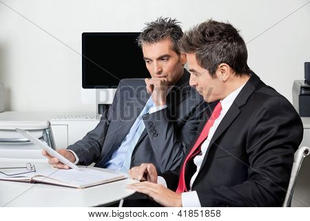 Two thoughtful businessmen using digital tablet at desk in office