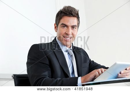 Portrait of handsome young businessman using digital tablet in office