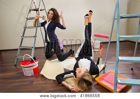 Young woman decorators posing with their equipment on a floor