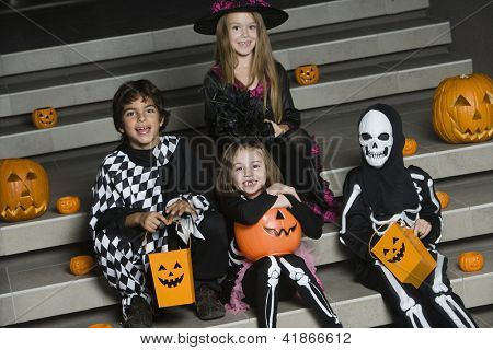 Portrait of happy friends sitting together on stairs in Halloween outfit