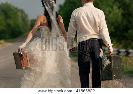 Close up of young newlywed couple holding  suitcases of cash on countryside road