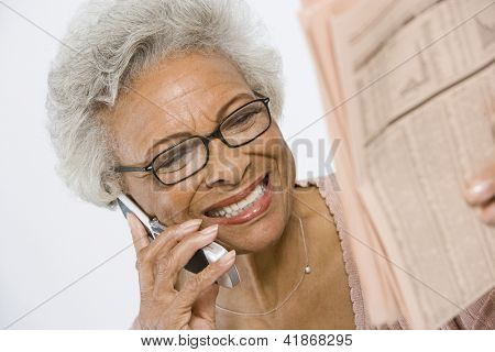 Happy African American senior woman reading newspaper while using cell phone
