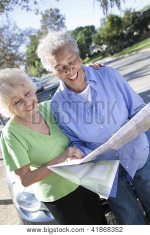 Happy senior woman holding road map with friend standing besides by the car