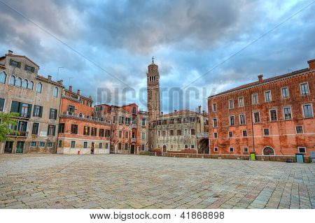 Small plaza among old typical colorful buildings and tall belfry on background under beautiful cloudy sky at evening in Venice, Italy.