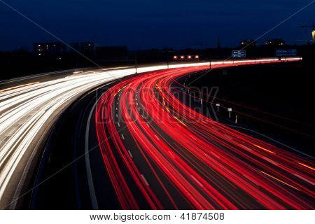 many cars are driving at night on a highway and create light trails.