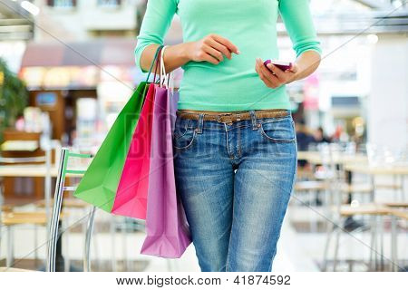 Close-up shot of a modern shopper with a mobile phone and colorful shopping bags