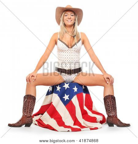 Young cowgirl sitting on a american flag. Retro style picture.