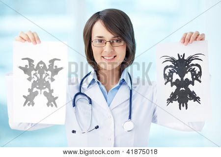 Smiling psychologist showing papers with Rorschach inkblots