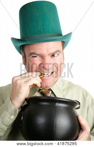 Irish man dressed as a leprechaun for St. Patrick's Day, biting a coin from his pot of gold.  White background.