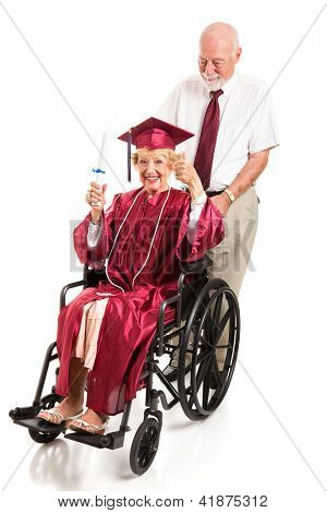 Disabled senior lady graduate gives a thumbs up as her husband pushes the wheelchair.  Full body isolated on white.